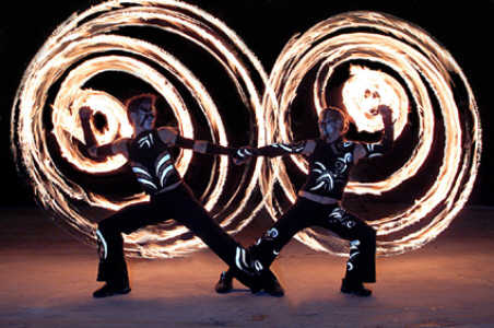 Two performers stand in circles of flame