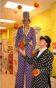 Steve juggls 5 balls while being overlooked by a stiltwalker