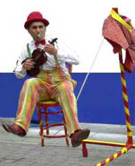 Francis Maxey playing music whilst sitting on a chair on a slack rope!